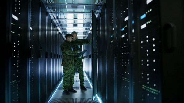 IT grün militär Server Kontrolle racks rechenzentrum In Data Center Two Military Men Work with Open Server Rack Cabinet. One Holds Military Edition Laptop