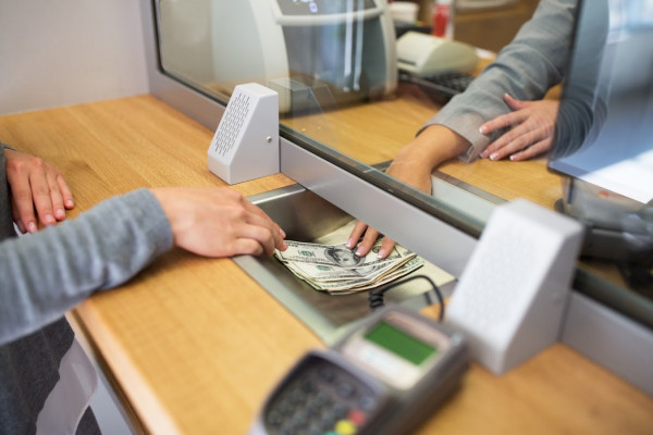 Schalter Geld Cash Kreditkarte EC people, withdrawal, saving and finance concept - clerk giving cash money to customer at bank office or currency exchanger