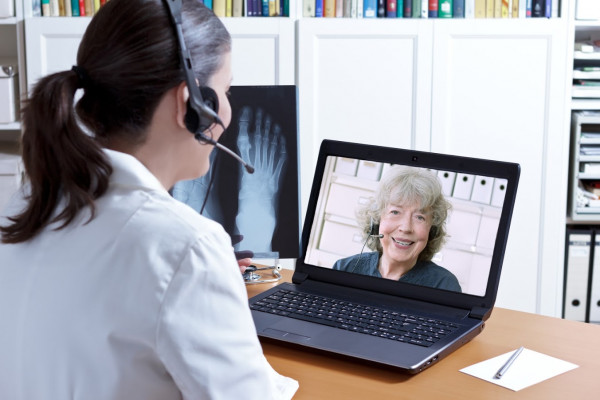 Skype Videokonferenz Konferenz Support Service Generation Jung Alt Gespräch Female doctor in her surgery office with headset in front of her laptop, an x-ray of a foot in hand, talking with a senior patient, telemedicine concept