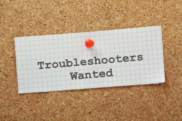 Talentsuche disruptiv Konflikt Troubleshooters Wanted typed on a piece of graph paper and pinned to a cork notice board. Business owners employ troubleshooters to look for and provide solutions to problems and improve processes