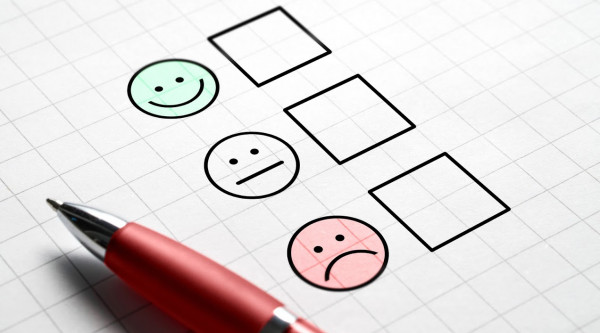 Bewertung Stimmung Emotion Zufriedenheit Mitarbeitezufriedenheit Customer satisfaction survey and questionnaire concept. Giving feedback with multiple choice form. Pen, paper and emotion smiley face icons