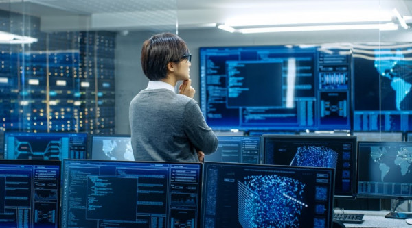 Experte Controlling Monitore Security In the System Control Room Technical Operator Stands and Monitors Various Activities Showing on Multiple Displays with Graphics. Administrator Monitors Work of Artificial Intelligence