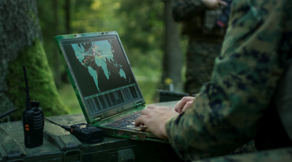 Militär Bundeswehr Sicherheit IT Military Operation in Action, Soldiers Using Military Grade Laptop Targeting Enemy with Satellite. In the Background Camouflaged Tent on the Forest