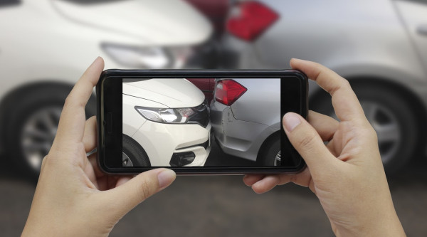 Unfall Versicherung Verkehr Smartphone Fotografieren Close up hand holding smartphone and take photo at The scene of a car crash and accident, car accident for car insuranc claim